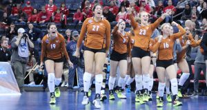 The Texas bench rushes the court after the final point in the Longhorns' upset over Nebraska.