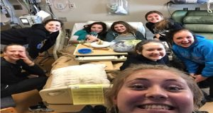 Rhea Jansen (in bed with green gown) is surrounded by her Kootenai Elite 16 teammates at a Spokane hospital just before their first match at PNQ. Jansen was diagnosed with lymphoma and began chemotherapy treatment not long after her teammates left to play.